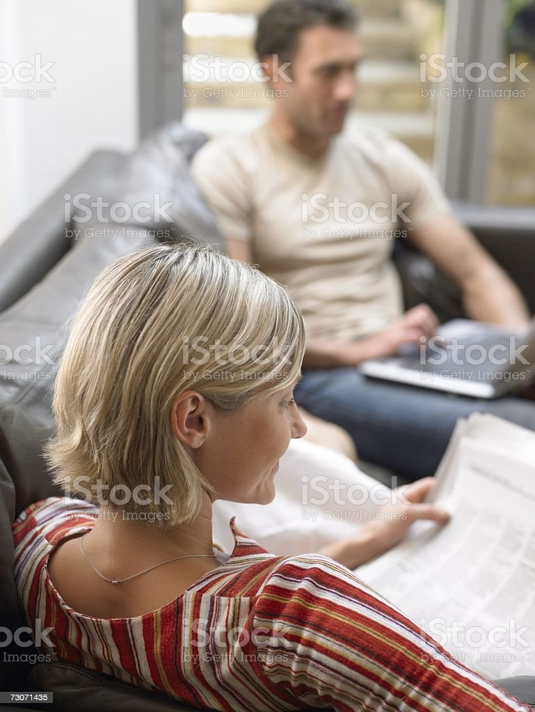Couple with newspaper and laptop stock photo