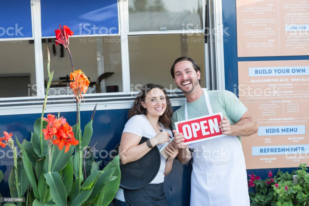 Couple with open sign in front of a food truck stock photo