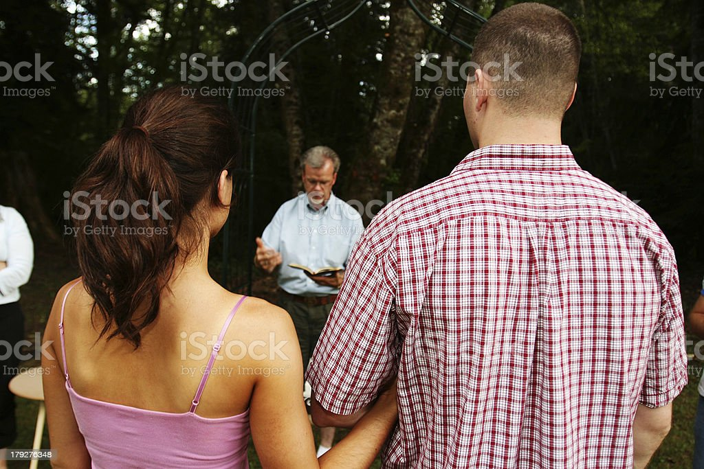 Couple with Priest Rehearsing for the Wedding stock photo
