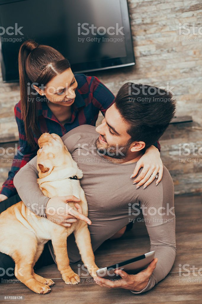 Couple with puppy surfing on the internet via tablet PC stock photo