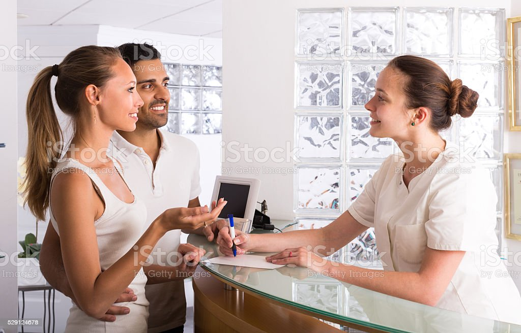 Couple with receptionist at clinic stock photo