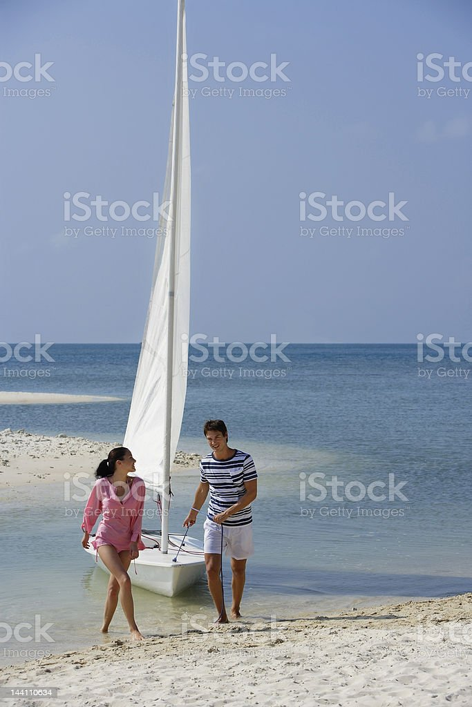 couple with sailboat on beach stock photo