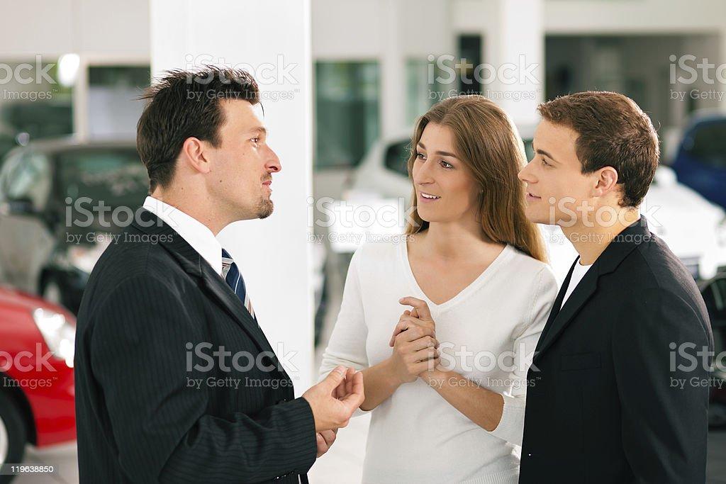 Couple with salesman at car dealer stock photo