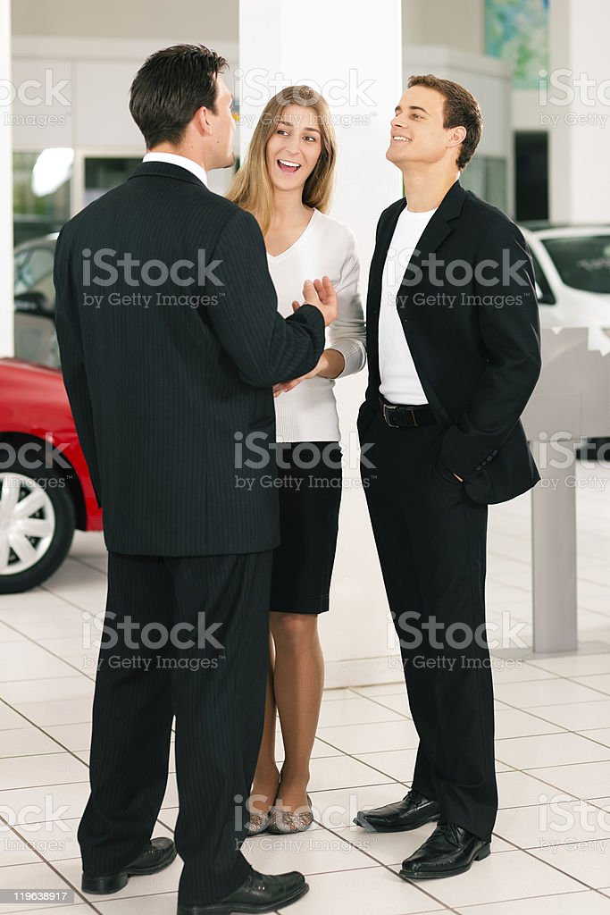 Couple with salesman at car dealer royalty-free stock photo