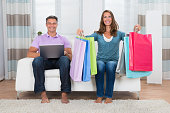 Couple With Shopping Bags And Laptop On Couch