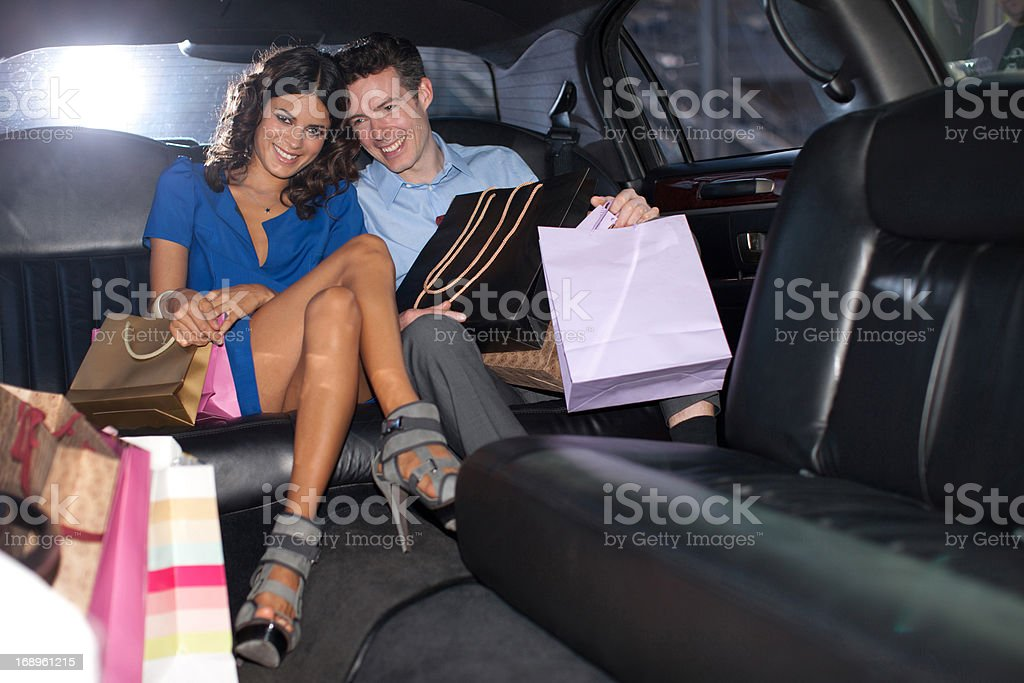 Couple with shopping bags in backseat of limo royalty-free stock photo
