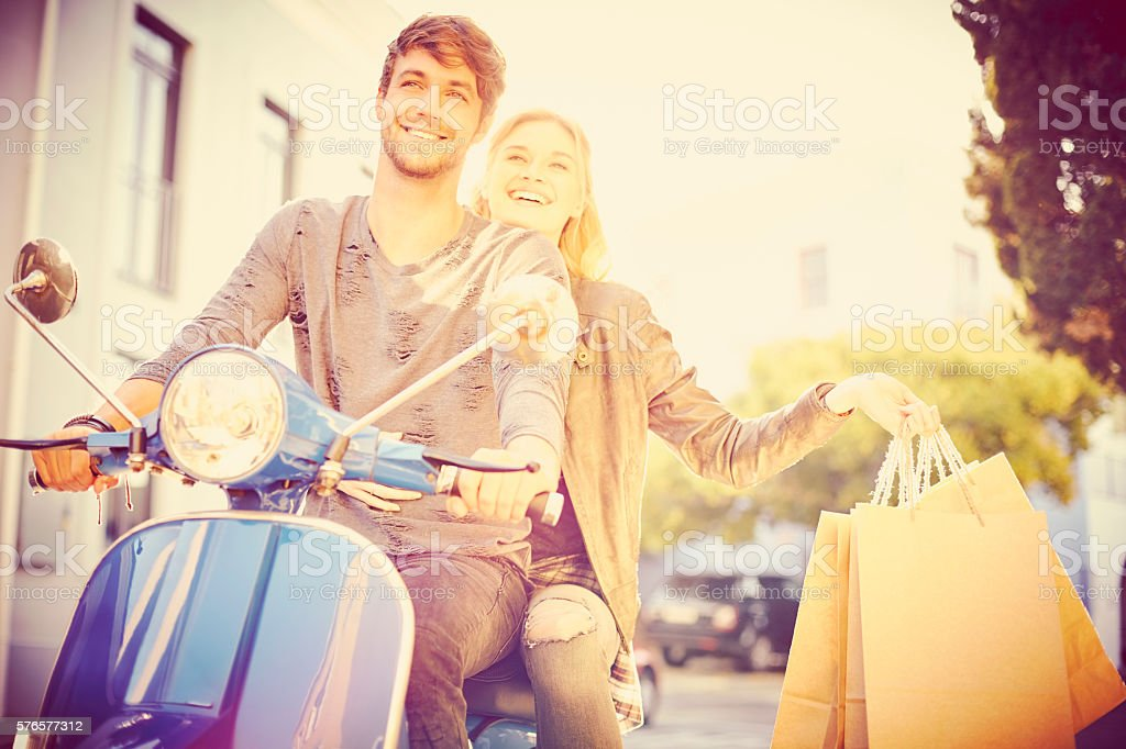 Couple with shopping bags riding motor scooter stock photo