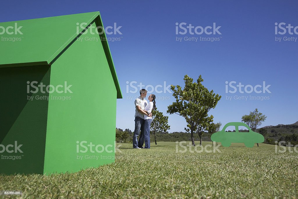 Couple with small model house and cutout car stock photo