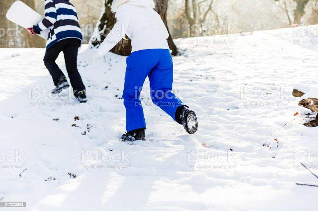 Couple with snowboards running stock photo