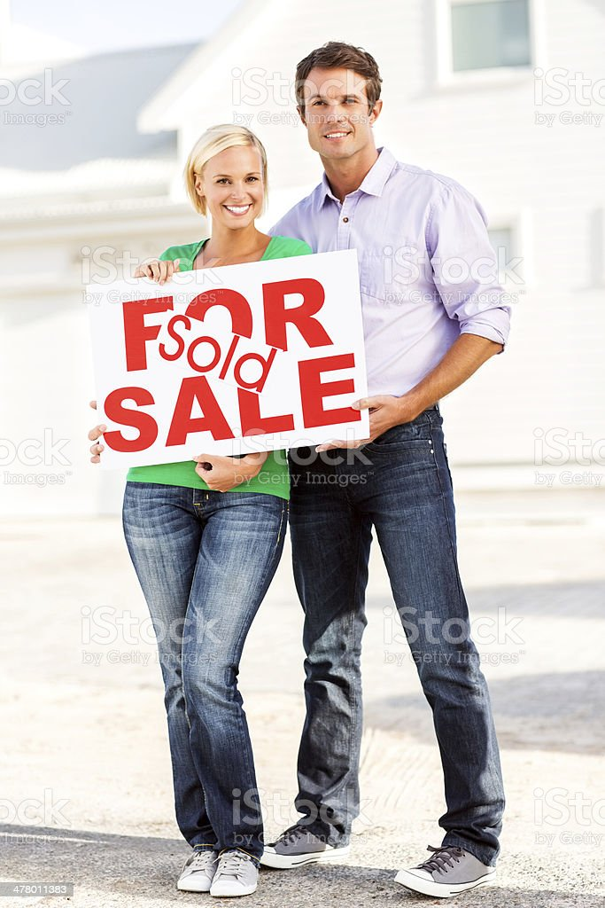 Couple With Sold And For Sale Sign royalty-free stock photo