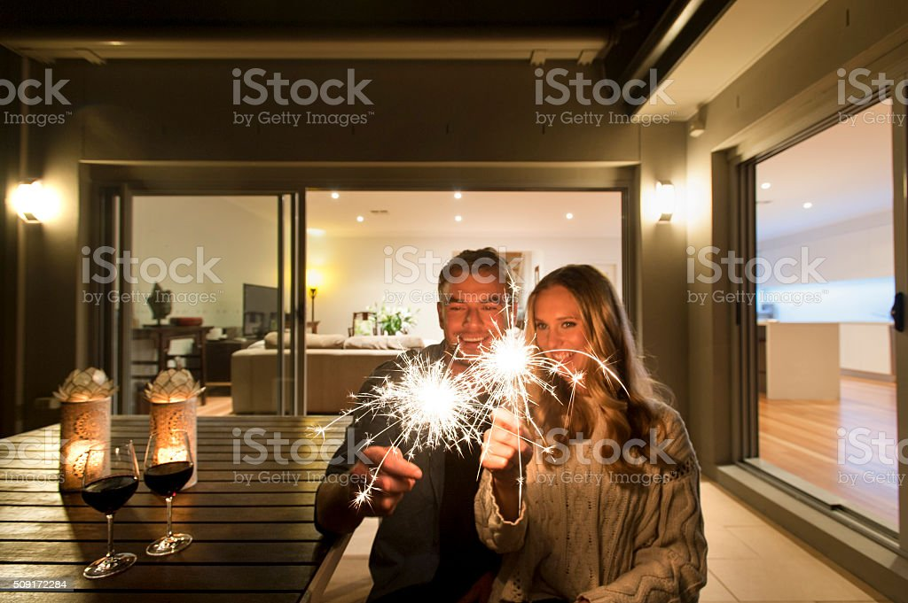 Couple with sparklers outside their home at night. stock photo