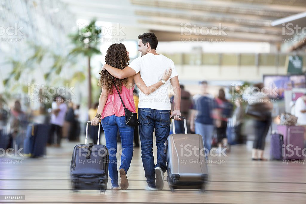 Couple with suitcases inside airport royalty-free stock photo