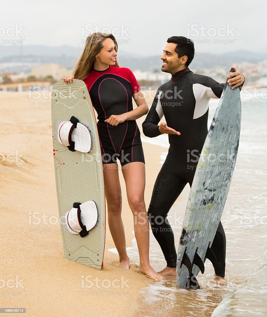 Couple with surf boards on the beach stock photo