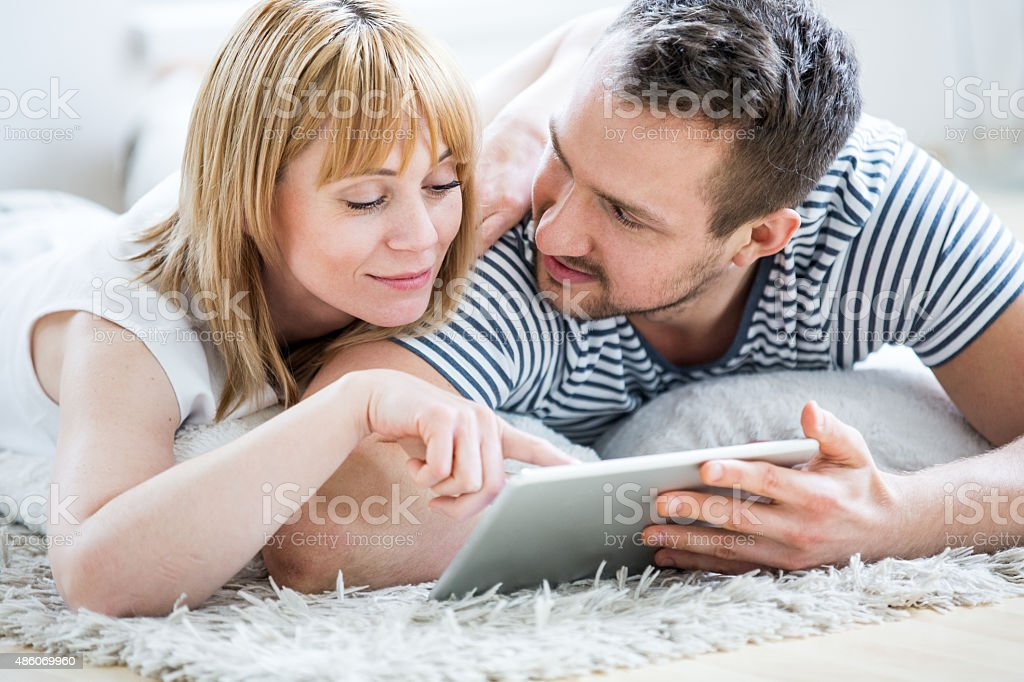 Couple with tablet lying on floor and surfing the net stock photo