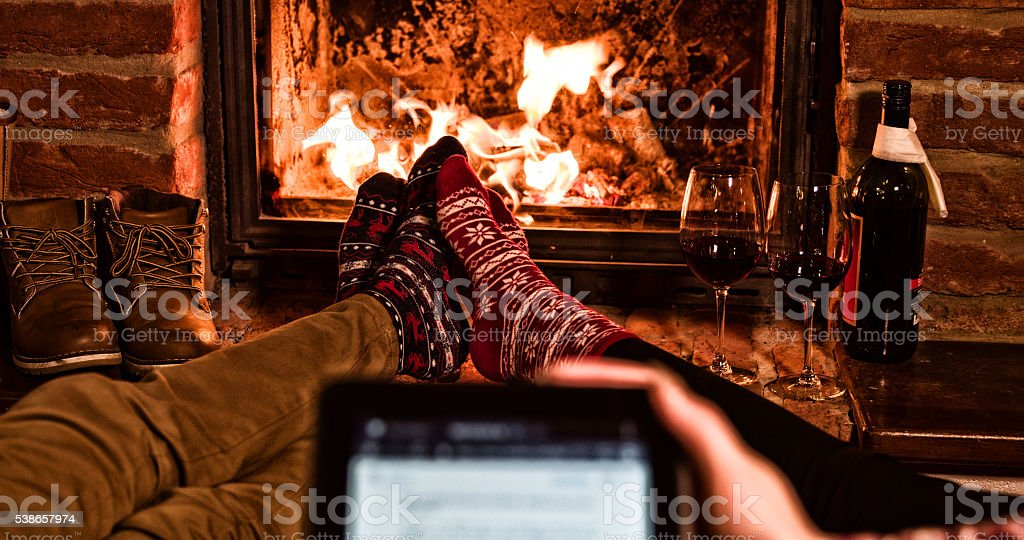 Couple with tablet PC by fireplace during Xmas stock photo