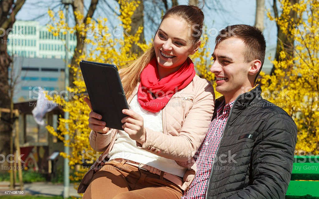 couple with tablet sitting on bench outdoor stock photo