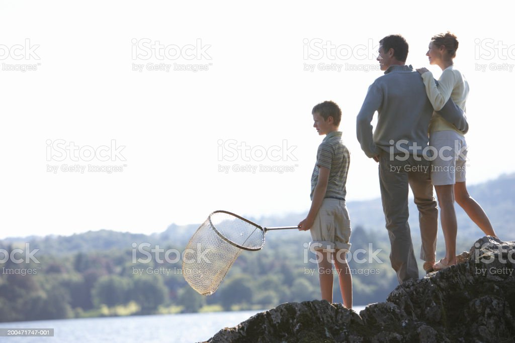 Couple with teenage son (13-15) on rocks by lake royalty-free stock photo