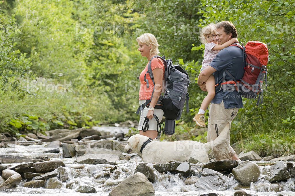A couple with their child about to cross a river stock photo