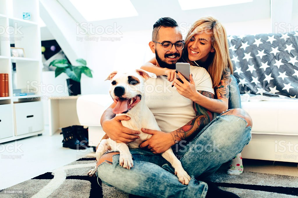 Couple with their dog at home stock photo