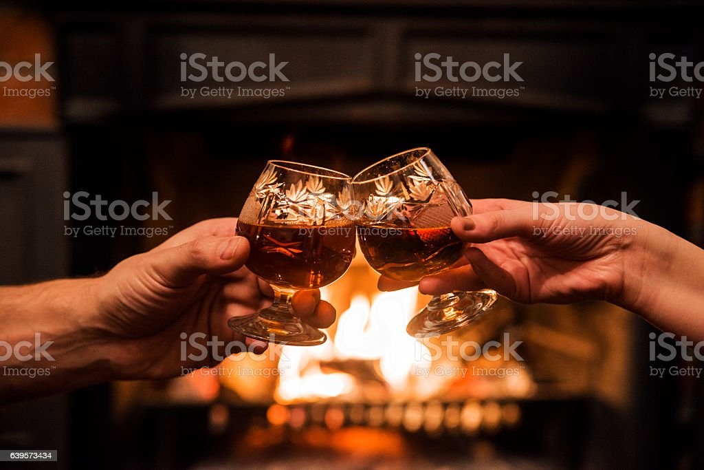 Couple with Two glasses of alcoholic drink  in front fireplace stock photo