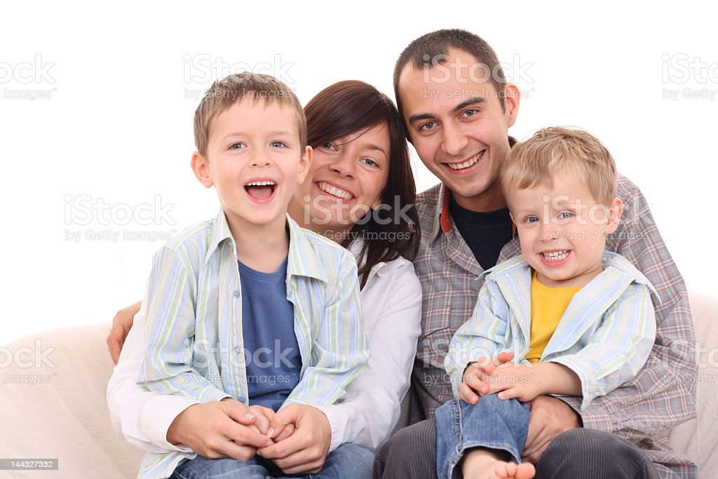 Couple with two young boys posing on a sofa royalty-free stock photo
