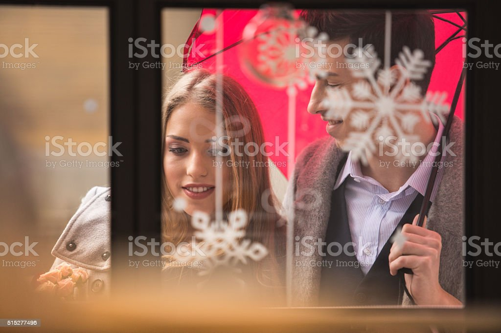 Couple with umbrella by the shop window stock photo