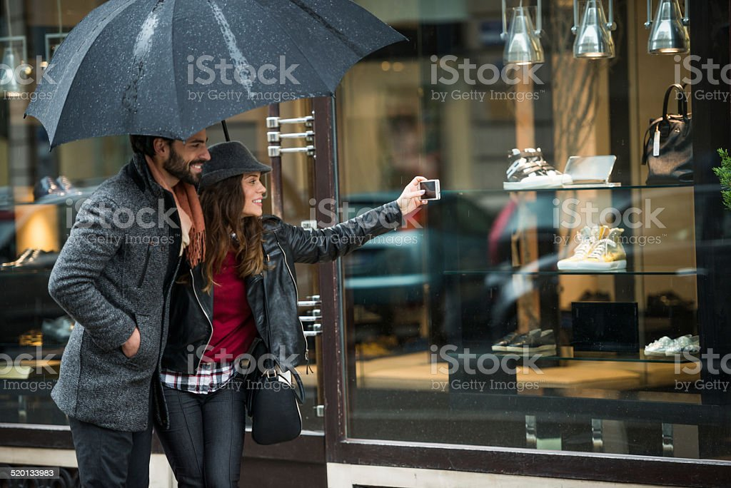 Couple with umbrella photographing the products in the store stock photo
