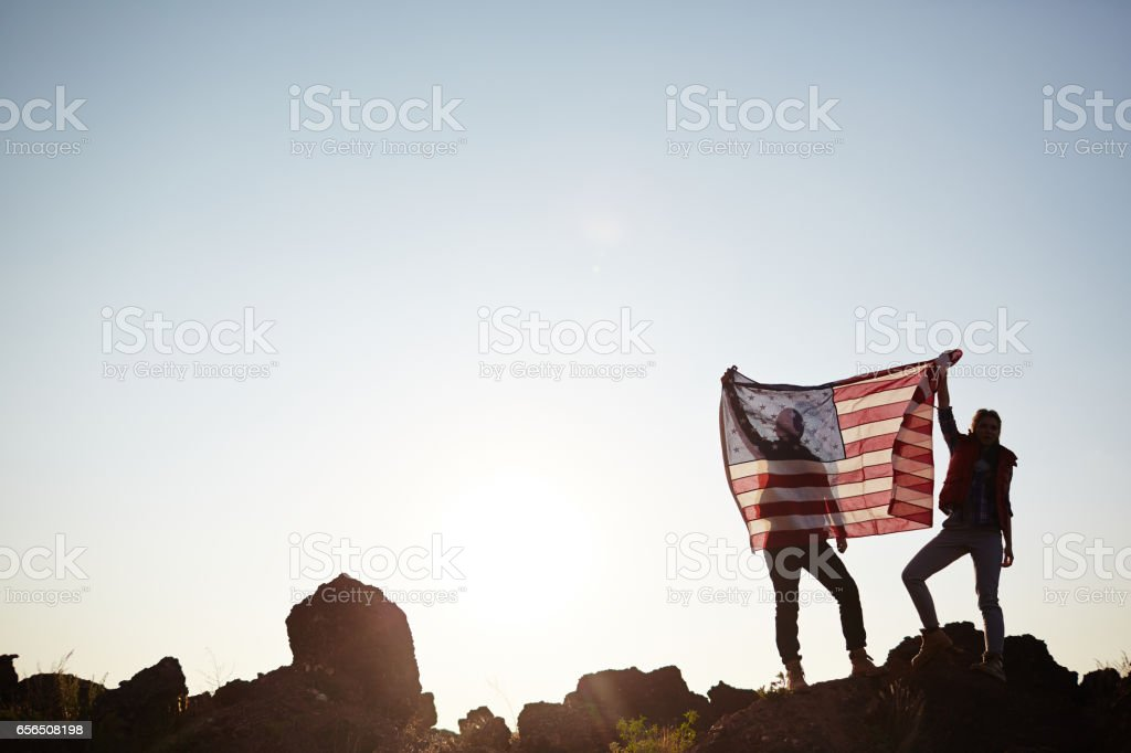 Couple with USA Flag on Mountain Top stock photo
