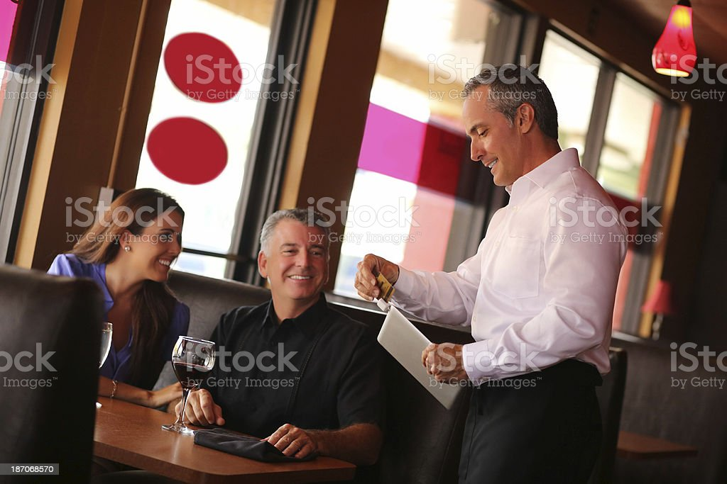 Couple With Waiter Swiping Credit Card On Digital Tablet stock photo