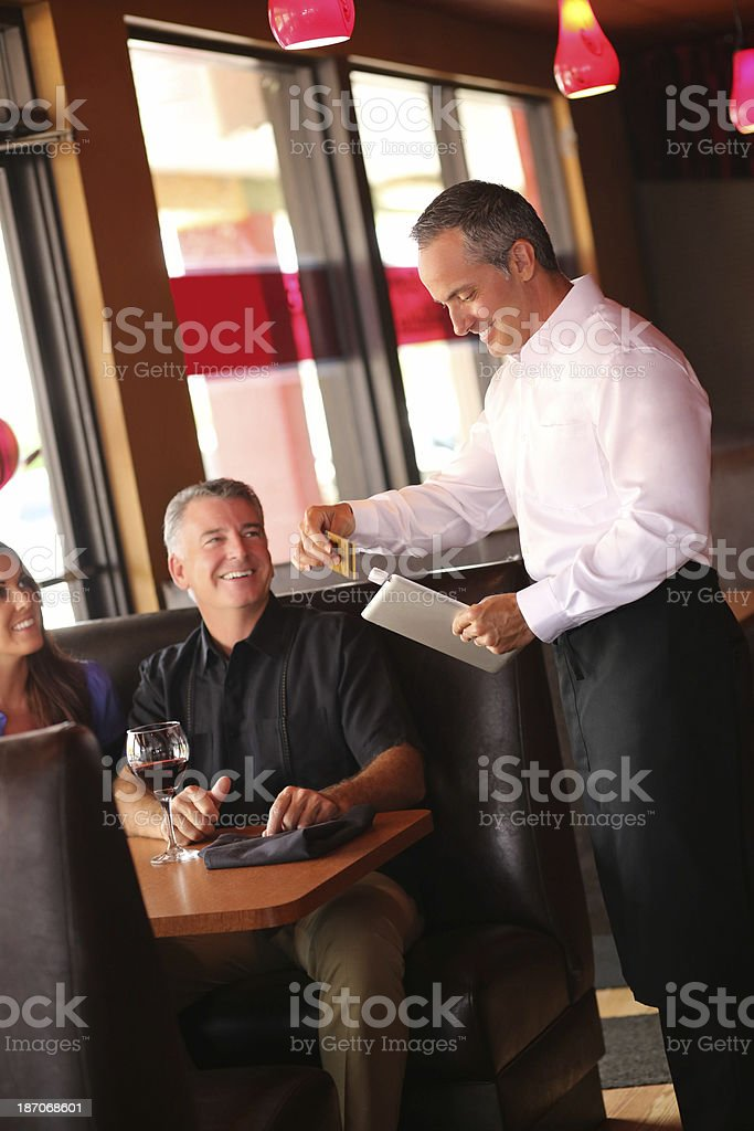 Couple With Waiter Swiping Credit Card On Tablet Computer stock photo