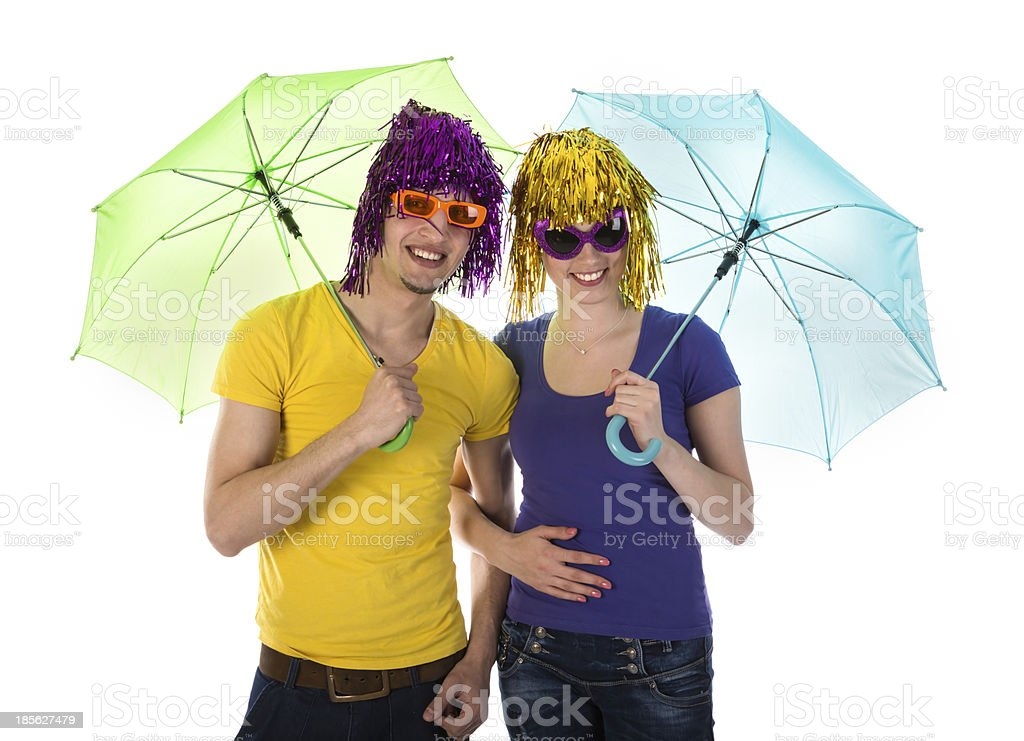Couple with wigs, sunglasses and umbrellas royalty-free stock photo