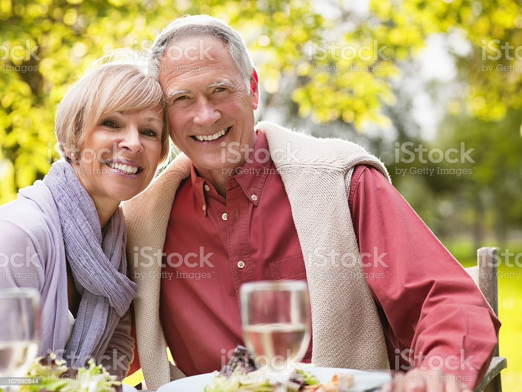 Couple with wine glasses and food on table at park, portrait royalty-free stock photo