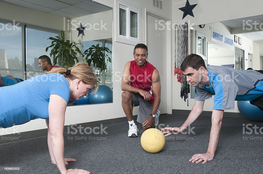 \'A couple working out with their personal trainer, doing balancing...