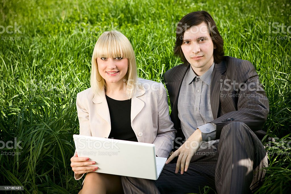 couple working on laptop in the grass field royalty-free stock photo