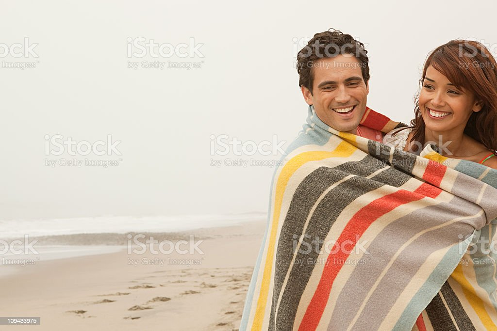 Couple wrapped up in colorful blanket on beach stock photo