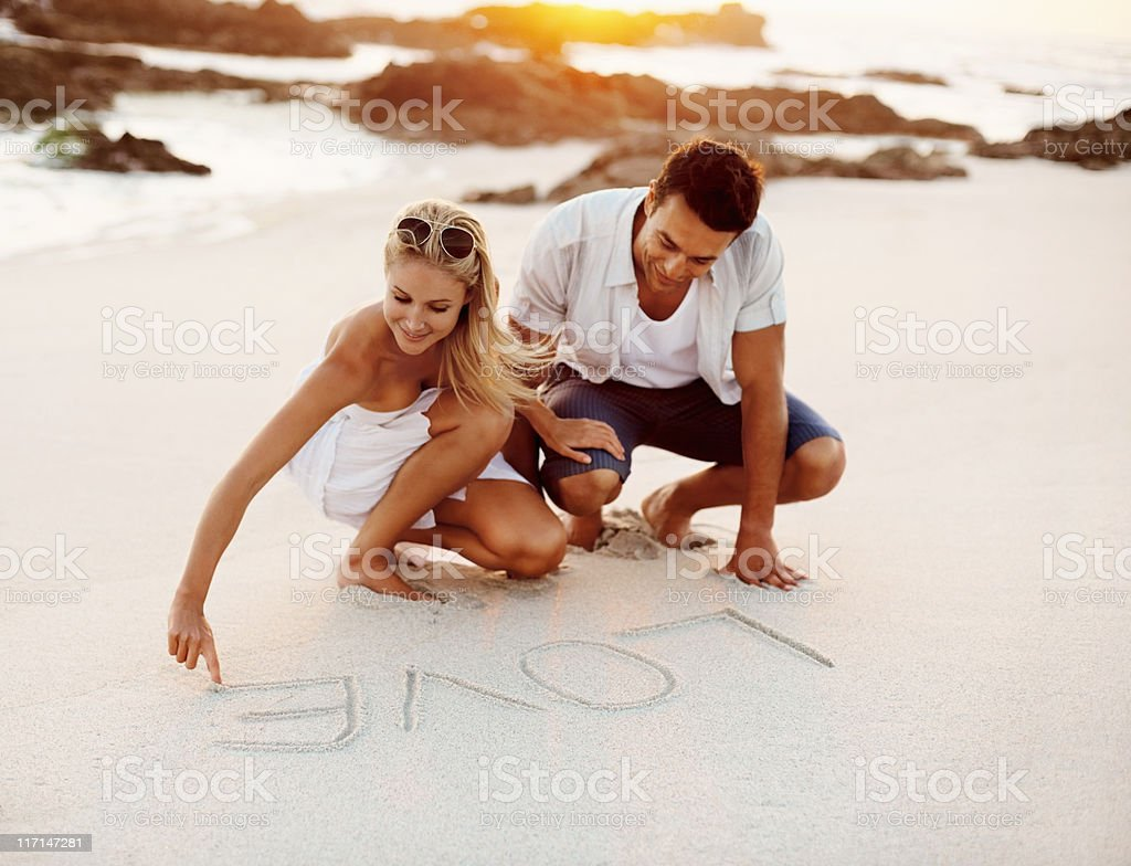 Couple writing love in sand royalty-free stock photo