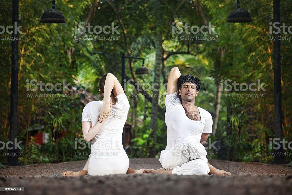 Couple yoga gomukhasana cow pose stock photo