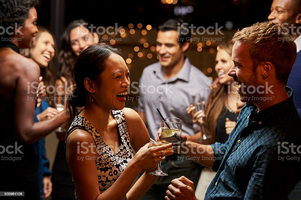 Couples Dancing And Drinking At Evening Party stock photo