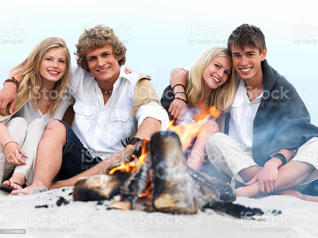Couples enjoying bonfire at beach in winter royalty-free stock photo