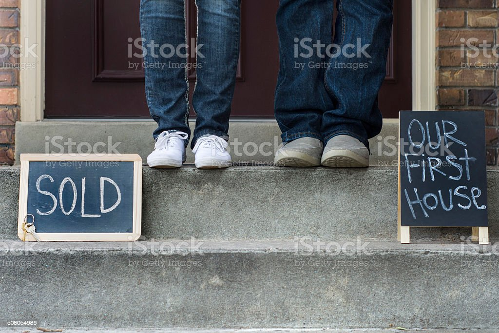 couples feet in front of house stock photo