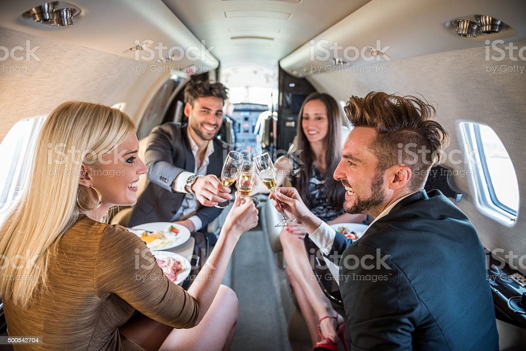 Couples having a toast in private jet airplane stock photo