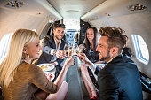Couples having a toast in private jet airplane