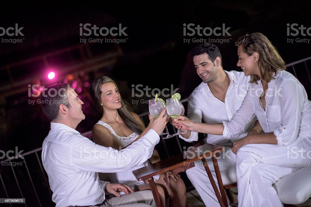 Couples having dinner and making a toast stock photo