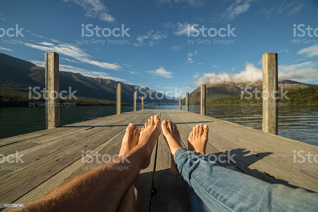 Couple's legs relaxing on a wooden lake pier stock photo