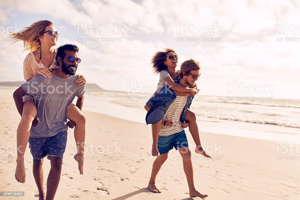 Couples piggybacking on sea shore stock photo