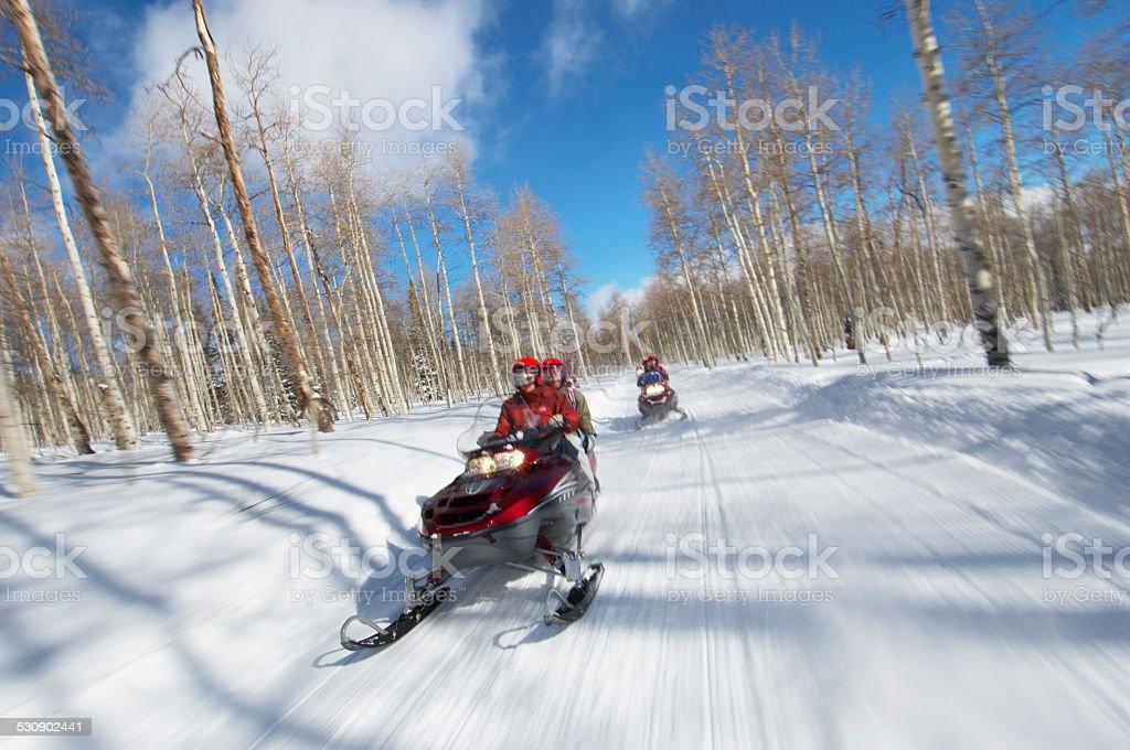Couples Racing on Snowmobiles stock photo