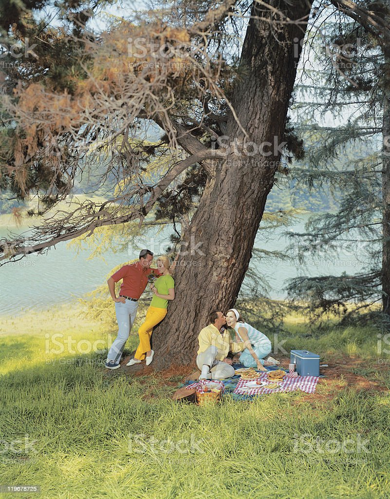 Couples resting under tree stock photo