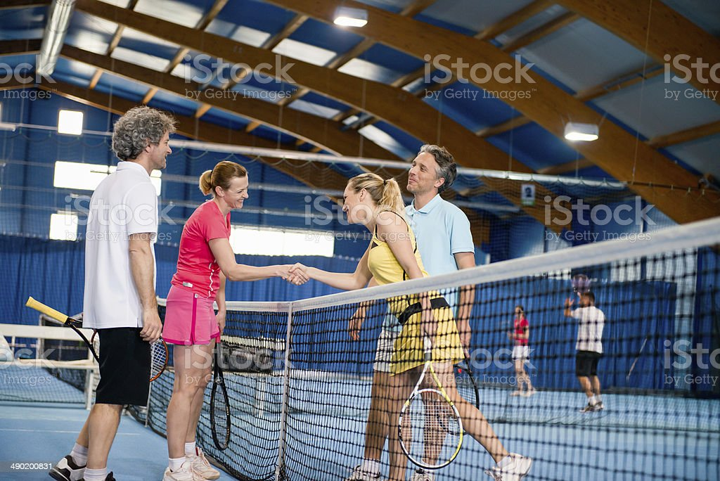 Couples shaking hands at tennis royalty-free stock photo
