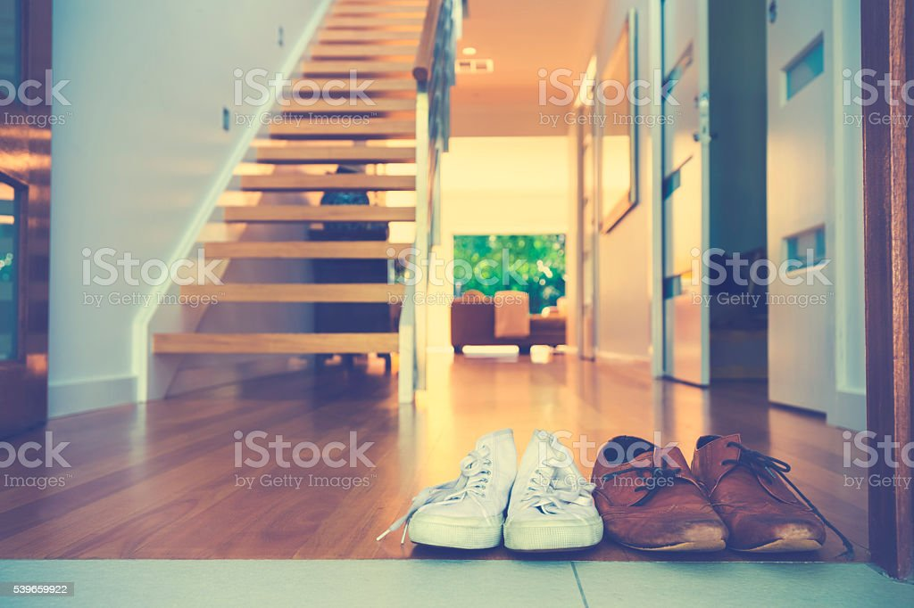Couples shoes at the front door of a house stock photo