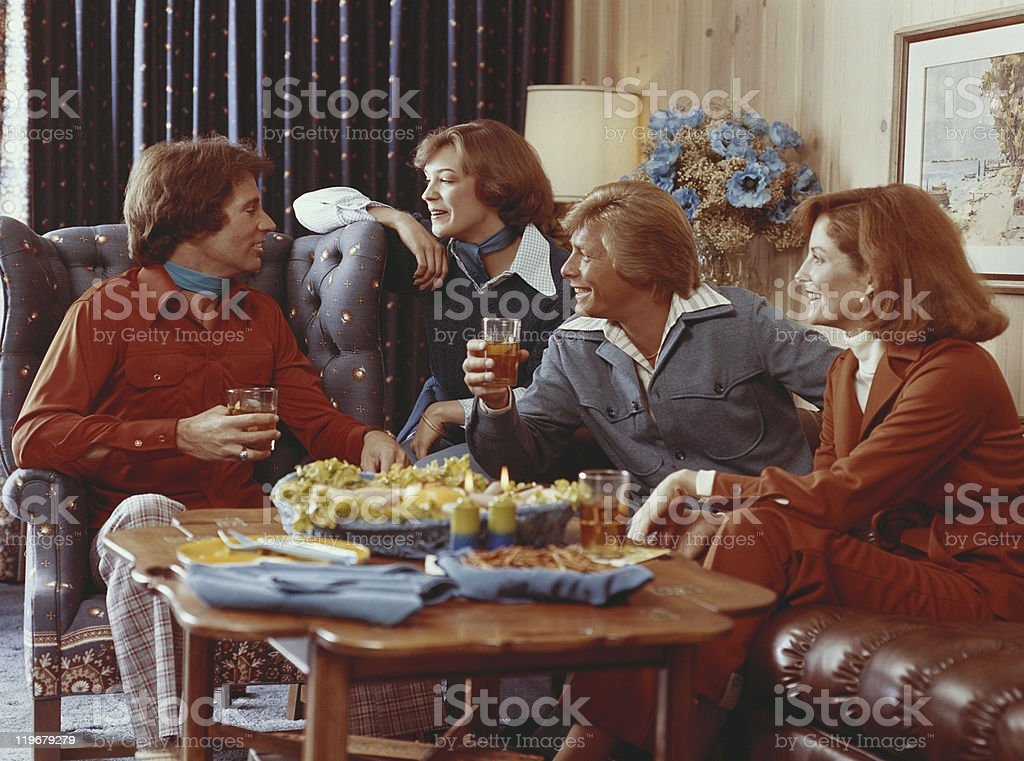 Couples sitting in living room and having drink stock photo